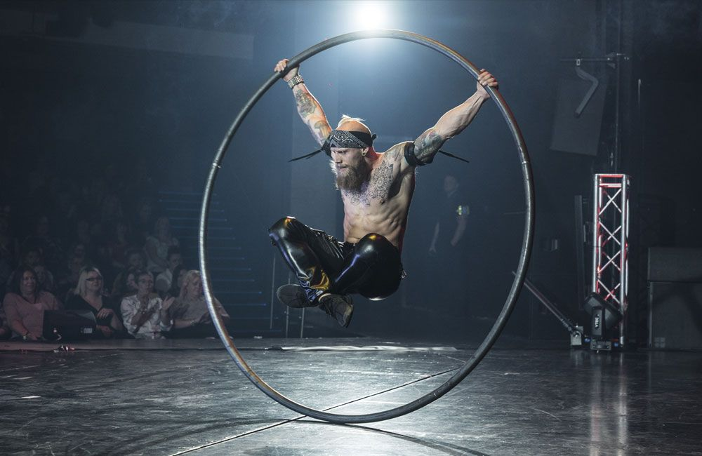 A man performs with a cyr wheel on stage