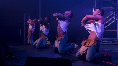 Male strippers rip their shirts off during a performance on stage
